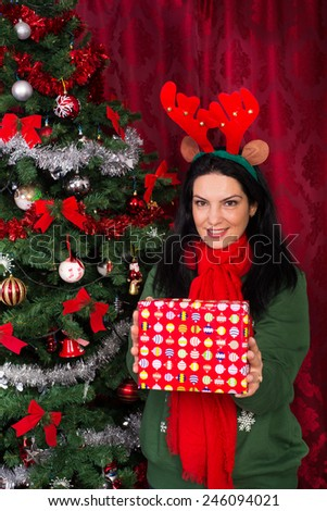 Happy woman with reindeer ears showing Christmas gift in front of camera - stock photo