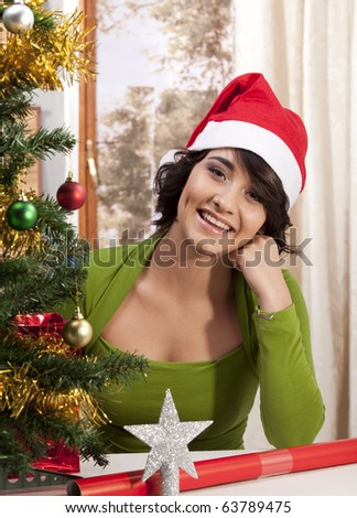 Happy woman with Santa hat sitting next to Christmas tree. - stock photo