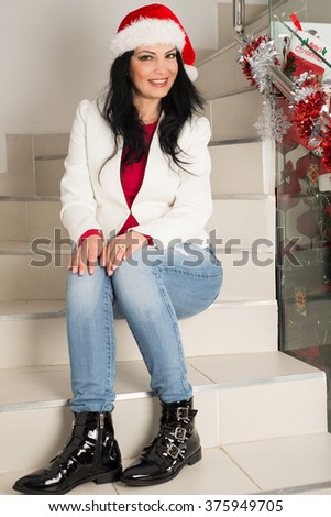 Happy woman with santa hat sitting on stairs home - stock photo