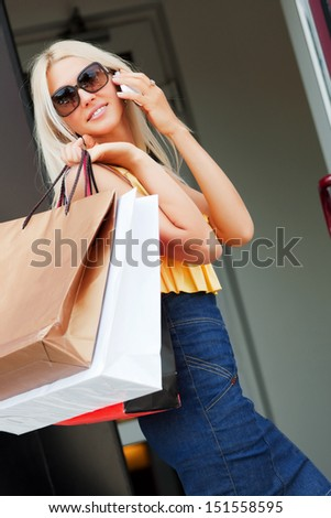Happy woman with shopping bags calling on the phone - stock photo