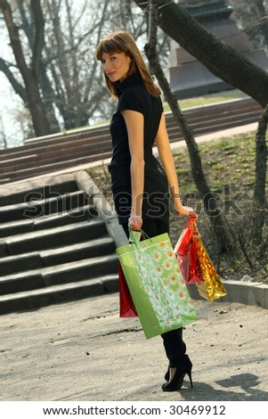 happy woman with shopping bags in a city park