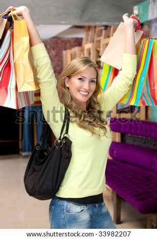 Happy woman with shopping bags in a mall - stock photo