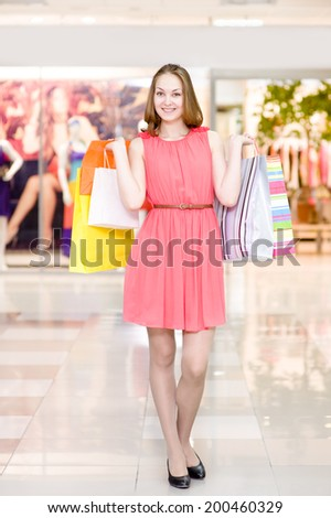 Happy woman with shopping bags  in a supermarket