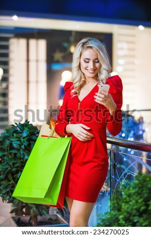 Happy woman with shopping bags using cell phone at a shopping center - stock photo