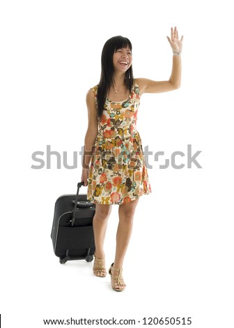 happy woman with small luggage on wheels waving, isolated on white background - stock photo