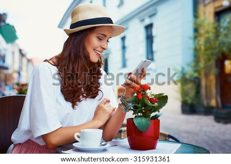 Happy woman with smartphone in outdoor cafe - stock photo