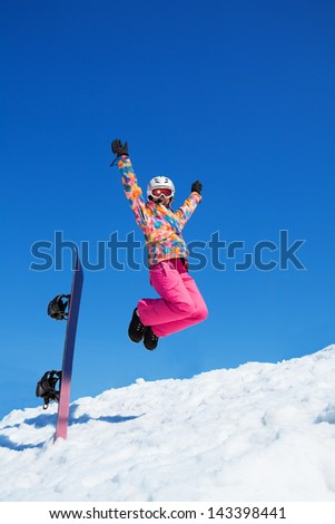 Happy woman with snowboard jumping in snow in mountains on blue sky - stock photo