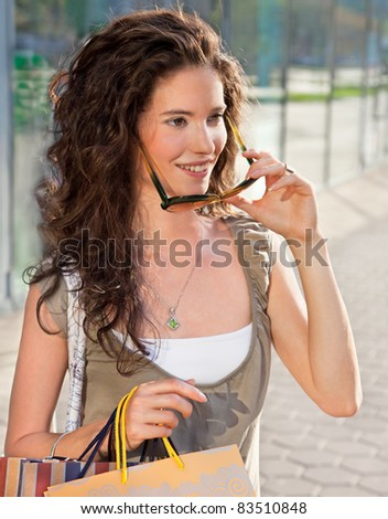 Happy woman with sunglasses in shopping holding bags - stock photo