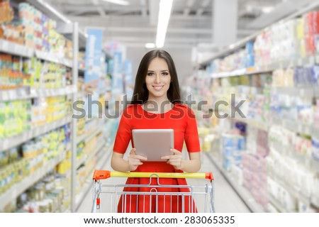 Happy Woman with Tablet Shopping  at The Supermarket - Young girl in a market store with a PC tablet in a department store  - stock photo