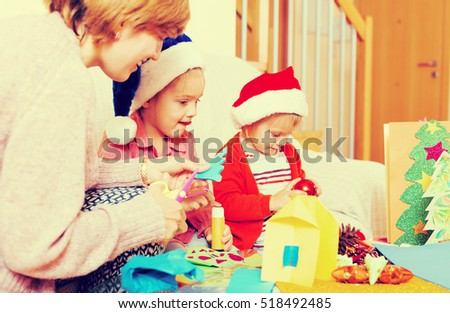 Happy woman with two daughters preparing for Christmas at home