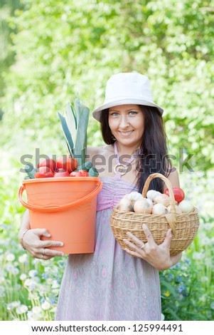 Happy woman with vegetables harvest in garden - stock photo