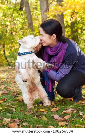 Happy woman with west highland white terrier dog in autumn forest