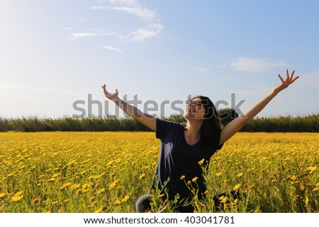 Happy woman with yellow flowers in Cyprus meadow.