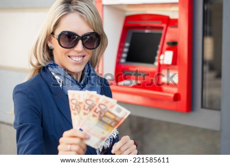 Happy woman withdrawing money from ATM - stock photo