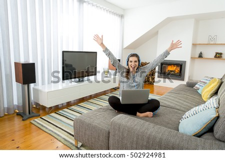 Happy woman working at home with a laptop while listen music