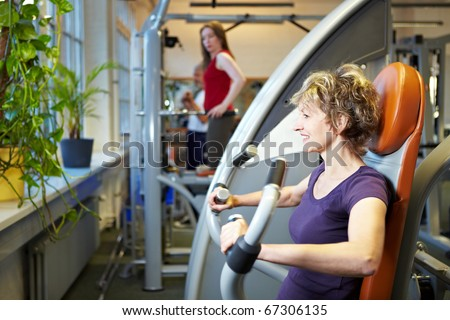 Happy woman working out on rowing machine in gym - stock photo