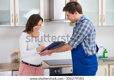 Happy Woman Writing On Clipboard In Front Of Young Plumber Standing In Kitchen - stock photo