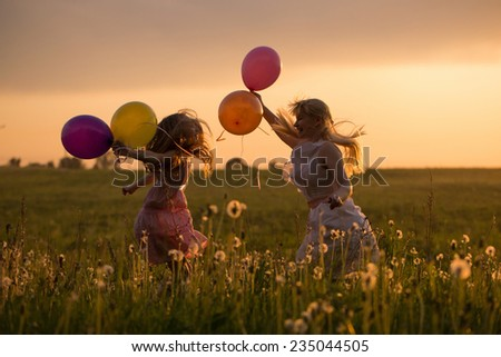 happy women and girl jumping with balloons outdoor - stock photo