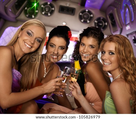 Happy women celebrating in limousine, smiling, looking at camera. - stock photo