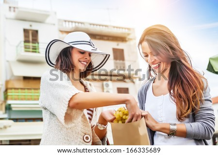 Happy women choosing a fruit outdoors in the bio market - stock photo