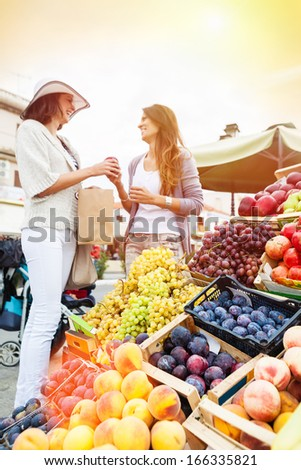 Happy women choosing a fruit outdoors in the bio market,sunset light. Focus on the grape. Lens flare - stock photo
