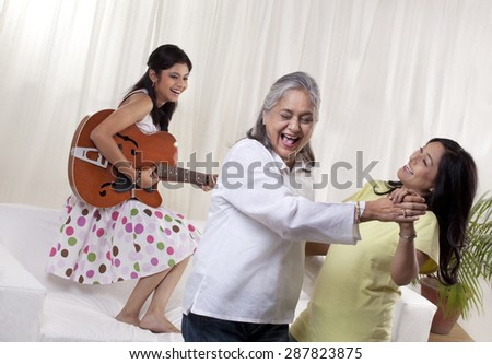 Happy women dancing while girl playing guitar - stock photo