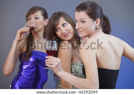happy women dancing with glasses wine at the disco - studio shot - stock photo