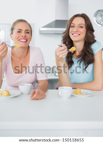 Happy women eating cake and having coffee together in the kitchen - stock photo