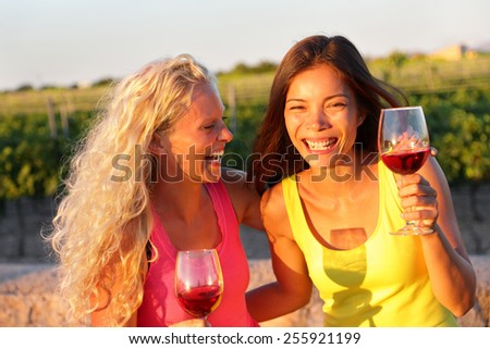 Happy women friends drinking red wine laughing in vineyard in summer. Young laughing girlfriends drinking rose wine from glass outside. - stock photo