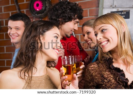 Happy women gazing on the each other and holding the cocktails - stock photo