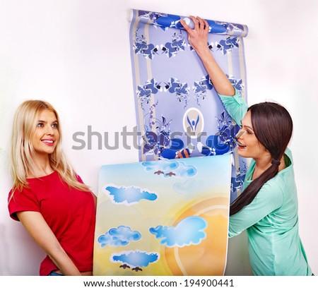 Happy women glues wallpaper at home. - stock photo