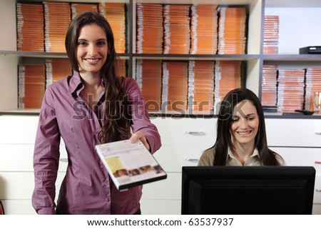 Happy women handing over dvd at the video rental store - stock photo