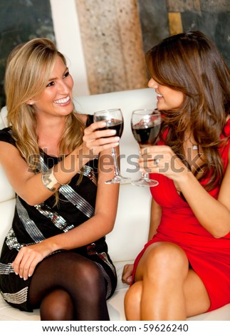 Happy women in a bar having a drink and toasting - stock photo