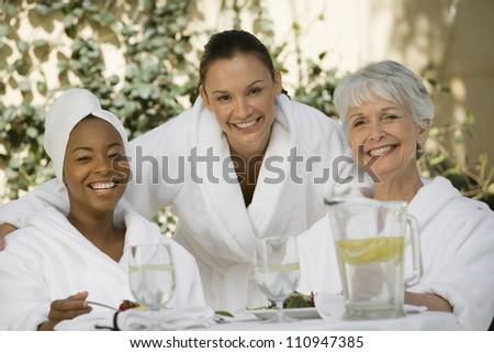 Happy women in bathrobe eating - stock photo