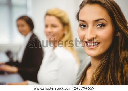 Happy women in computer room smiling at camera in the office