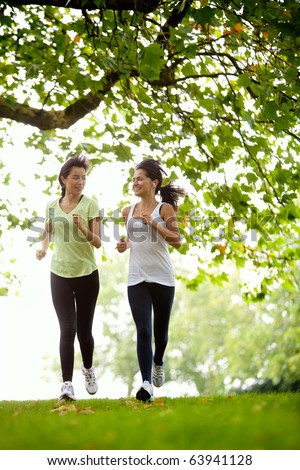 Happy women jogging at the park - fitness concepts - stock photo