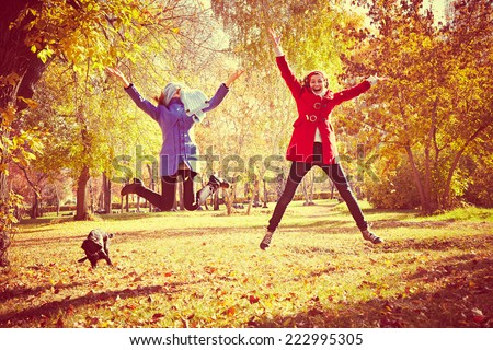 happy women jumping outside at autumn fall  - stock photo