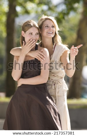 Happy women looking into distance pointing with shocked expression - stock photo