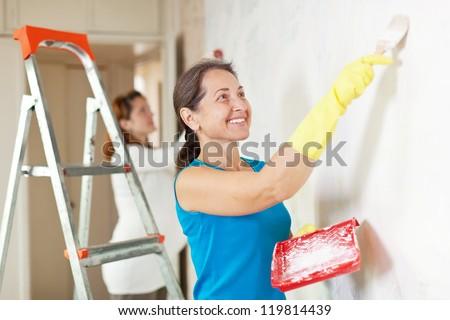 Happy women  making repairs at room - stock photo