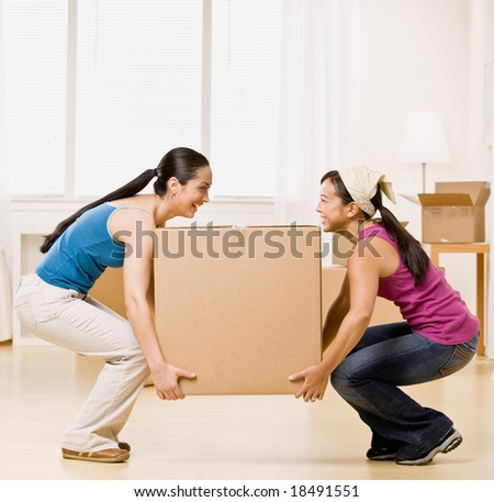 Happy women moving into new home and carrying large, heavy cardboard box - stock photo