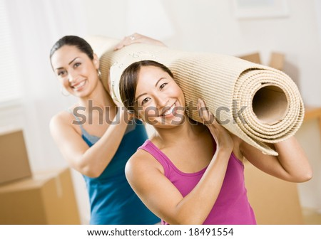 Happy women moving into new home and carrying rub - stock photo