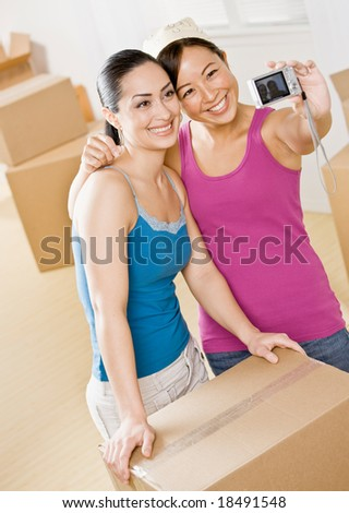 Happy women moving into new home and taking self-portrait near cardboard boxes - stock photo
