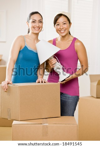 Happy women moving into new home and unpacking cardboard box - stock photo