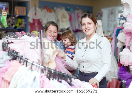 Happy women of three generations chooses clothes at store. Focus on woman - stock photo