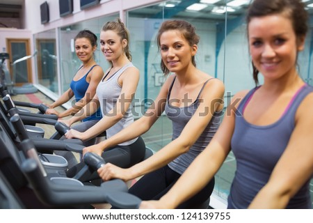 Happy women on exercise bikes in gym