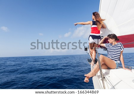 Happy women on the bow of a Sailboat pointing at something.Copy space - stock photo