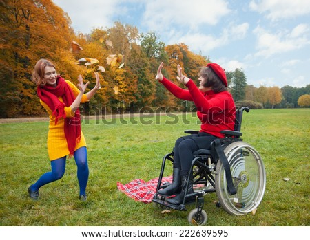 happy women play maple leaves in autumn Park - stock photo