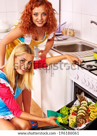 Happy women prepare fish in oven.