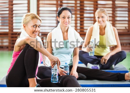 Happy women relaxing and talking after fitness training - stock photo