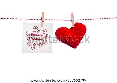 Happy Women's Day. Happy Women's Day on paper , hanging on a rope with red hearts.